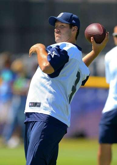 Dallas Cowboys quarterback Tony Romo throws a pass during NFL football training camp, Thursday, July
