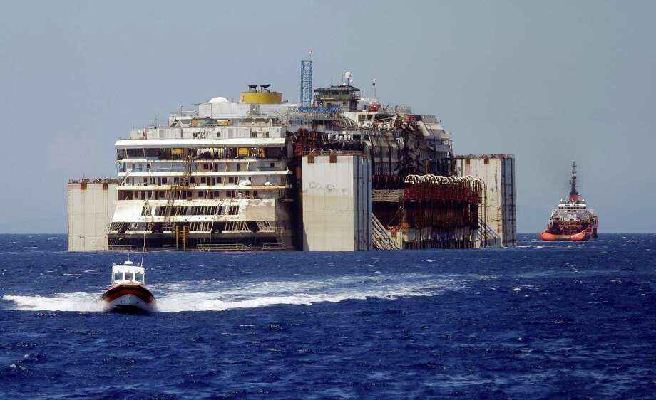The Costa Concordia is towed by tugboats away from Giglio Island, Italy, where it crashed Jan. 13, 2012 Photo: Gregorio Borgia, STF / AP