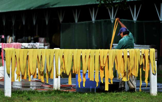 A groom washes his leg wraps Thursday morning July 24, 2014 at the Saratoga Race Course in Saratoga Springs, N.Y.      (Skip Dickstein / Times Union) Photo: SKIP DICKSTEIN