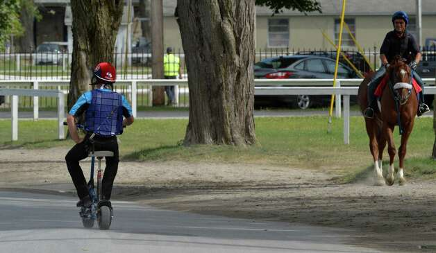 Exercise rider Freddy Buscail gets a look from another exercise rider as he uses a scooter to make his rounds for business Thursday morning July 24, 2014 at the Saratoga Race Course in Saratoga Springs, N.Y.      (Skip Dickstein / Times Union) Photo: SKIP DICKSTEIN