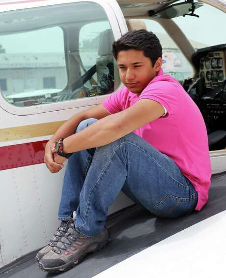 Haris Suleman, 17, sits on the wing of his airplane in Lahore, Pakistan, during his around-the-world flight. Photo: Courtesy Photo / Associated Press / The Citizens Foundation