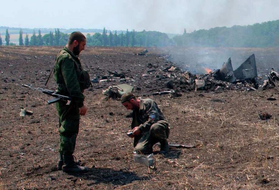 In this framegrab made from a video provided by press service of the rebel Donetsk People's Republic and icorpus.ru,  pro-Russians collect parts of the burning debris of a Ukrainian military fighter jet, shot down at Savur Mogila, eastern Ukraine, Wednesday, July 23, 2014. Two Ukrainian military Sukhoi-25 fighters have been shot down in the east, according to the country's Defense Ministry. (AP Photo/icorpus.ru, Press Service of the rebel Donetsk People's Republic) ORG XMIT: XAZ102 Photo: Icorpus.ru / Rebel Donetsk People's Republic, icorpus.ru