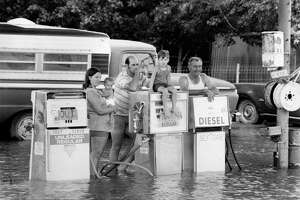 07/27/1979 - Alvin fuel pumps may have been out of gas Friday, but there was plenty of water for the taking. These residents paused at the partly submerged pumps to gaze at the deluge dropped on their city by tropical storm Claudette.