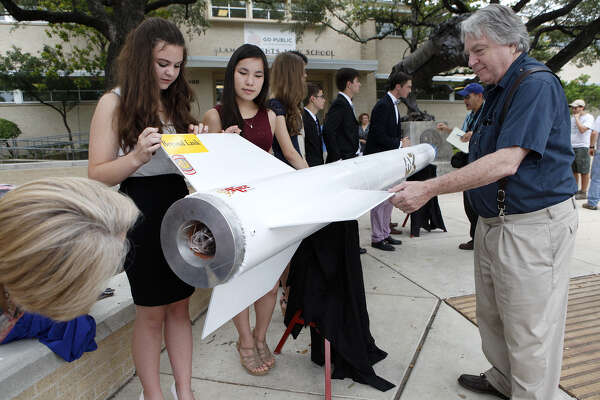 Alamo Heights High School aeroscience students Naomi Pringle (left) and Aiyin Graeber answer questions as the public and parents, such as Luke Soules (right), get a closer look at the students' two rockets.