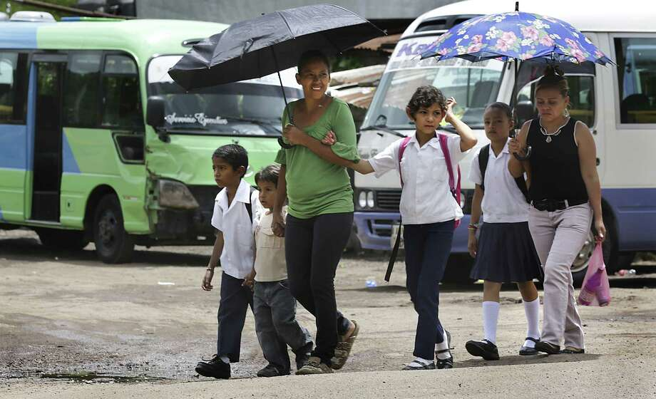 Walking with her school-age children, a mother glances across the street where national police are investigating a murder in Barrio Cerro Grande in Tegucigalpa, Honduras. Photo: Bob Owen / San Antonio Express-News / ©2013 San Antonio Express-News
