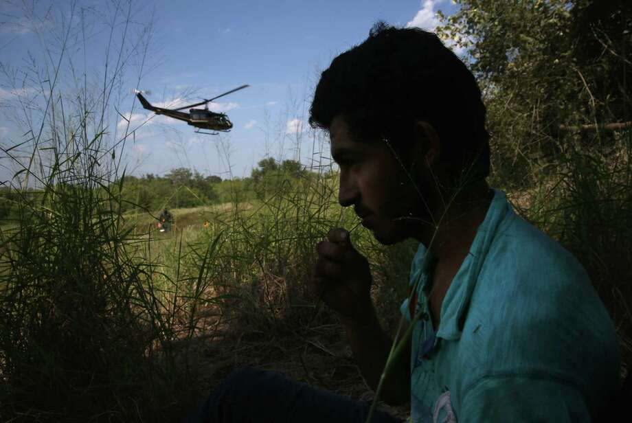 An undocumented immigrant takes refuge in the shade in Falfurrias as a copter takes other immigrants to a processing center. Photo: John Moore / Getty Images / 2014 Getty Images