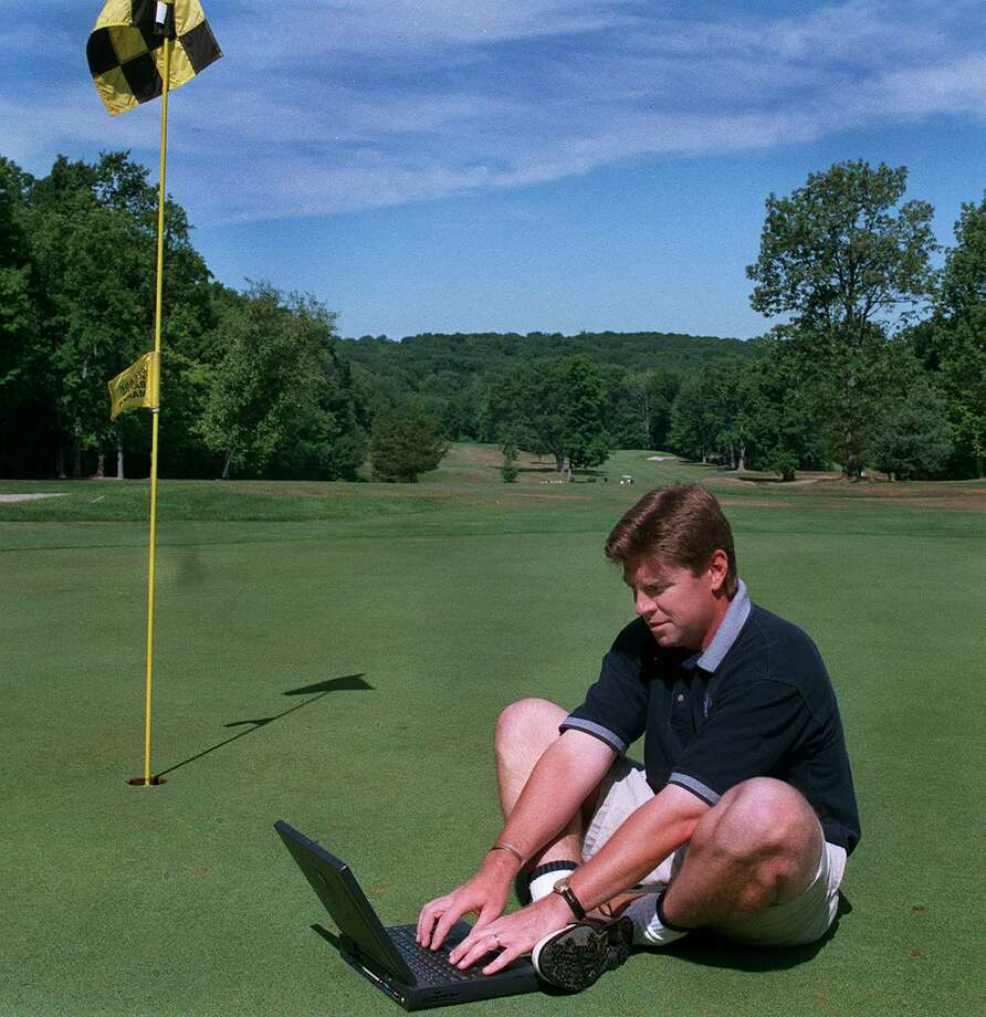 Greg Jacobson with laptop computer on the 18th hole at the Rigefield Golf course. Photo: File Photo\Michael Duffy, Michael Duffy/News-Times File Photo / The News-Times File Photo