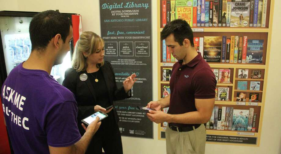 San Antonio Public Library's Caitlin Cowart guides YMCA employees Jeremy Cruz and Matthew Flores through the QR code scanning process at the D.R. Semmes Family YMCA. Photo: Jacob Beltran / San Antonio Express-News