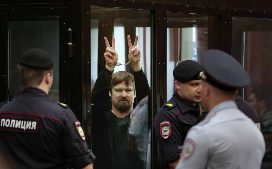 Russian opposition activist Leonid Razvozzhayev, in handcuffs, shows V-signs from a defendant's cage in a court room prior to a hearing in Moscow. Photo: Ivan Sekretarev / Associated Press / AP