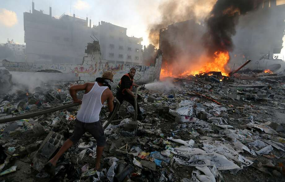 Palestinian men try to extinguish flames in an area damaged in an Israeli airstrike in Gaza City in the Gaza Strip on Thursday, July 24, 2014. Israeli tanks and warplanes bombarded the Gaza Strip on Thursday, as Hamas militants stuck to their demand for the lifting of an Israeli and Egyptian blockade in the face of U.S. efforts to reach a cease-fire. (AP Photo/Hatem Moussa) Photo: Hatem Moussa, Associated Press