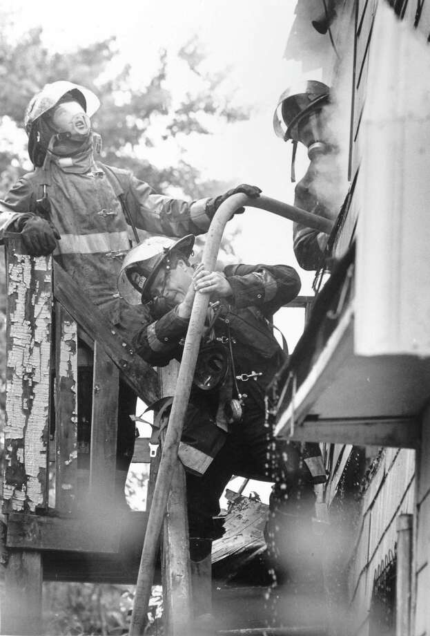 Firefighters pull a hose into the third floor of a house at 293 Fairfield Avenue on July 30, 1989 that left 23 people homeless. Photo: File Photo/Dru Nadler / Stamford Advocate File Photo