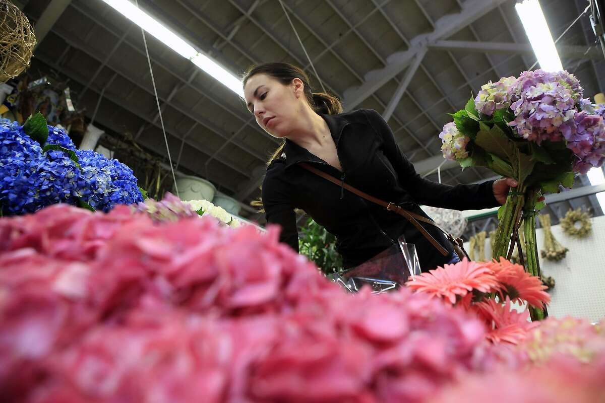 Floral designer Nicole Peacock of The Petal Pusher shops for flowers for a customers wedding at Brother's Floral in the Flower Mart in San Francisco, CA, Thursday, July 24, 2014.