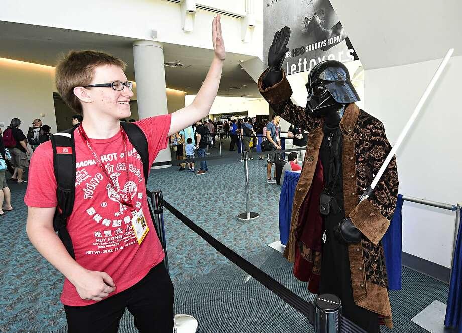 A fan high-fives another fan dressed as Star Wars' Darth Vader during preview night at the 2014 Comic-Con International Convention held  Wednesday, July 23, 2014 in San Diego. (Photo by Denis Poroy/Invision/AP) Photo: Denis Poroy, Associated Press