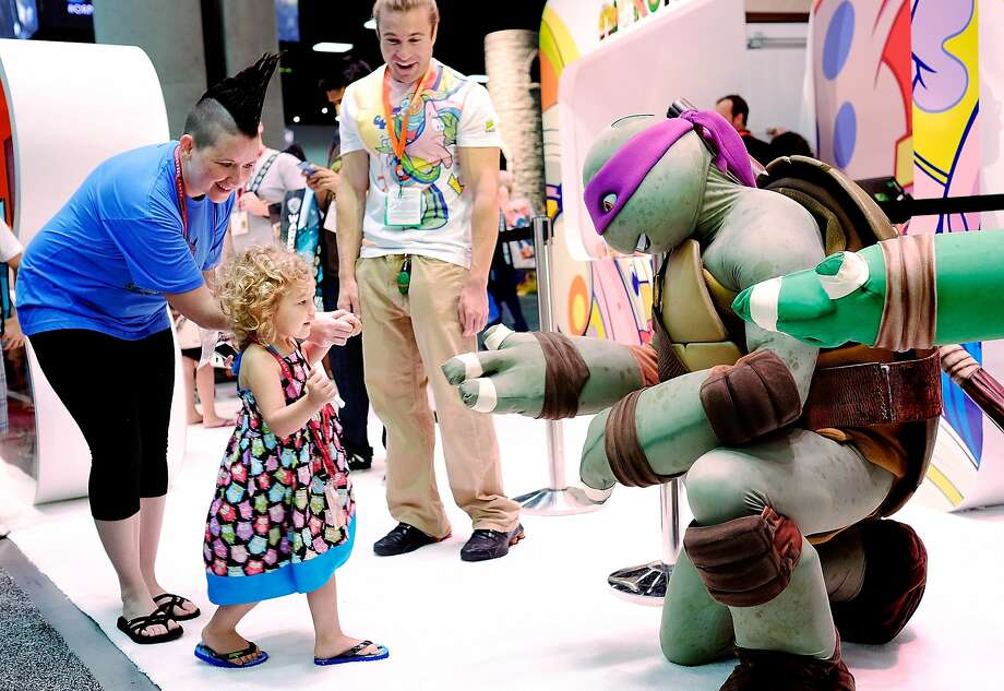 SAN DIEGO, CA - JULY 24: Two year old Ellie Campbell, along with her aunt Jen Pike of Austin, Texas, gets a high-five from the Teenage Mutant Ninja Turtle character Donatello during the 45th annual San Diego Comic-Con on July 24, 2014 in San Diego, California. An estimated 130,000 attendees are expected at this year's convention, which will celebrate the 75th anniversary of both Marvel Comics and the first Batman comic book. (Photo by T.J. Kirkpatrick/Getty Images) Photo: T.J. Kirkpatrick, Getty Images