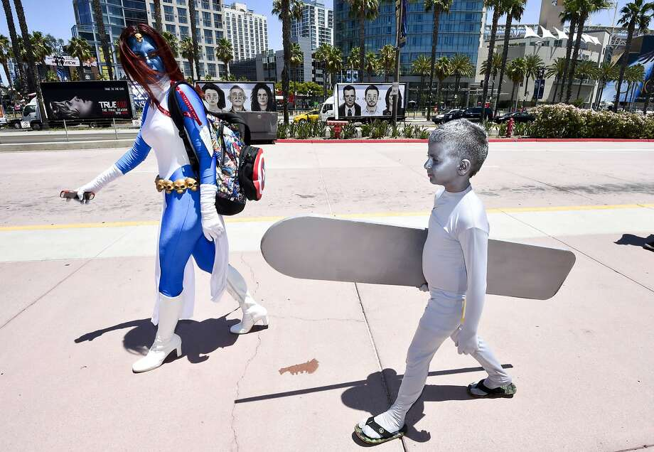 Dina Mills, left, and her son walk outside of the convention center on day 1 of the 2014 Comic-Con International Convention held Thursday, July 24, 2014 in San Diego. (Photo by Denis Poroy/Invision/AP) Photo: Denis Poroy, Associated Press