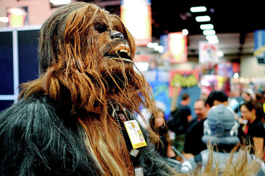 Christopher Petrone, of San Diego, CA, towering over attendees in his handmade, to-scale Chewbacca costume, gives a roar to fans during the 45th annual San Diego Comic-Con on July 24, 2014 in San Diego, California. An estimated 130,000 attendees are expected at this year's convention, which will celebrate the 75th anniversary of both Marvel Comics and the first Batman comic book. Photo: T.J. Kirkpatrick, Getty Images / 2014 Getty Images