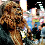 Christopher Petrone, of San Diego, CA, towering over attendees in his handmade, to-scale Chewbacca costume, gives a roar to fans during the 45th annual San Diego Comic-Con on July 24, 2014 in San Diego, California. An estimated 130,000 attendees are expected at this year's convention, which will celebrate the 75th anniversary of both Marvel Comics and the first Batman comic book.