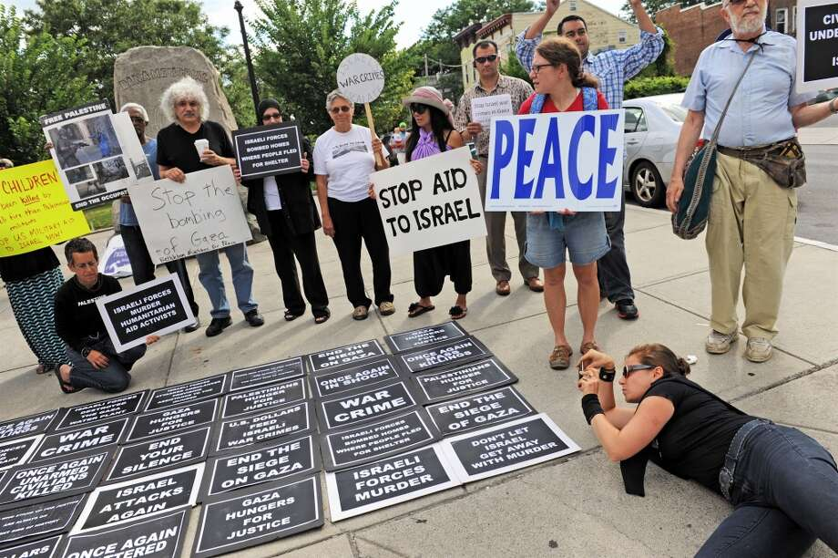Laying out signs, getting ready to make a show of opposition to the massacre of civilians in Gaza. Photo: Carl Strock