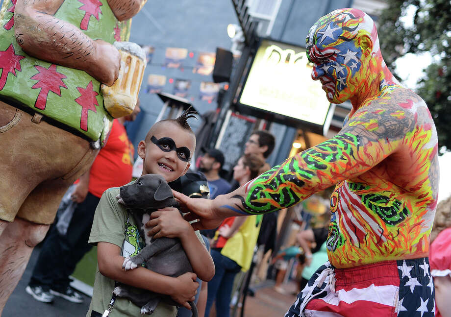 A man in body paint pets a puppy held by seven-year-old Ashton Ritz on the first day of the 45th annual Comic-Con, in San Diego, California July 24, 2014.  The four-day pop culture extravaganza celebrates film, TV, video games, comic books, costumes and other popular arts. More than 150,000 fans are expected to attend the sold-out event. Photo: ROBYN BECK, AFP/Getty Images / AFP
