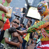 A man in body paint pets a puppy held by seven-year-old Ashton Ritz on the first day of the 45th annual Comic-Con, in San Diego, California July 24, 2014.  The four-day pop culture extravaganza celebrates film, TV, video games, comic books, costumes and other popular arts. More than 150,000 fans are expected to attend the sold-out event.