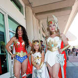 (L-R) Costumed fans Nicole Kiss, Alexa Kiss, and Nicolle Hanbury pose for photos outside the San Diego Convention Center on July 24, 2014 in San Diego, California.