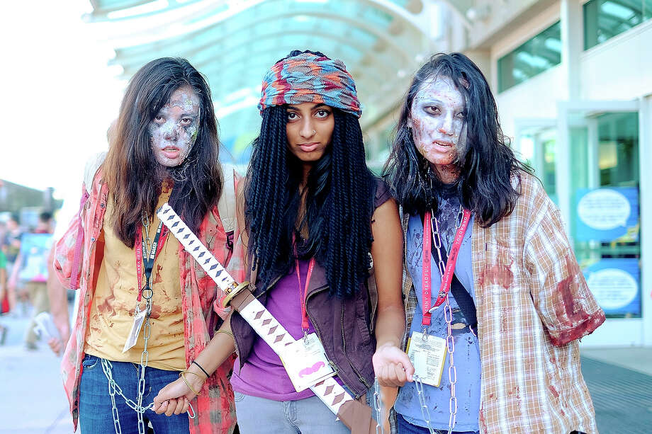 "Sirisha Verigonda, center, of San Diego, CA, poses as Michonne from the show ""The Walking Dead"" with two zombies, Emily Zheng, left, and Gina Huang, both of San Diego, during the 45th annual San Diego Comic-Con on July 24, 2014 in San Diego, California. An estimated 130,000 attendees are expected at this year's convention, which will celebrate the 75th anniversary of both Marvel Comics and the first Batman comic book. Photo: T.J. Kirkpatrick, Getty Images / 2014 Getty Images"