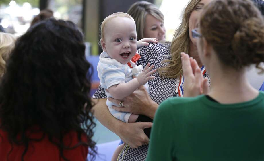 Owen Ezell laughs with caregivers at Medical City Children's Hospital in Dallas on Thursday, July 24, 2014. Owen and his formerly conjoined twin, Emmett, were brought to the hospital where they were surgically separated to celebrate their first birthday with those who helped care for them. (AP Photo) Photo: Associated Press
