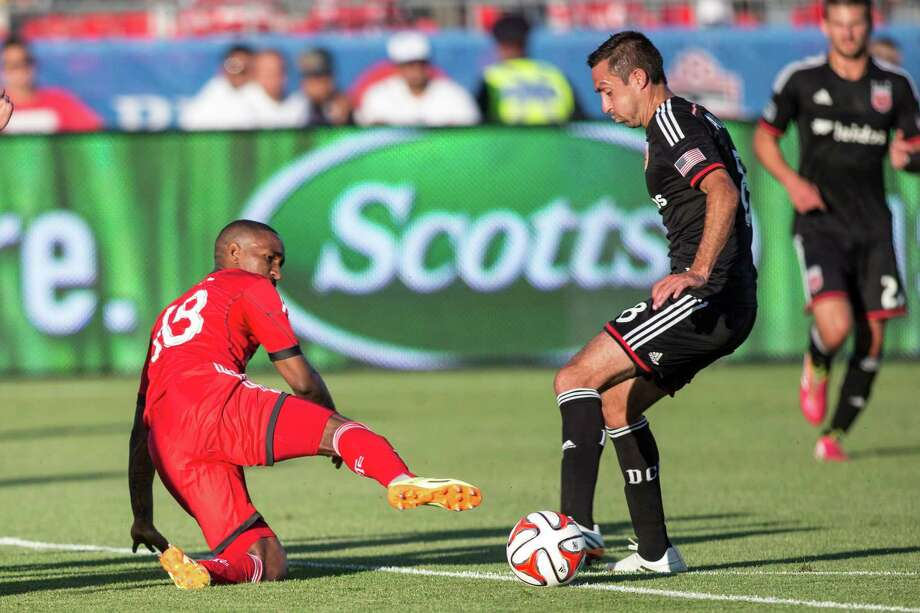 Toronto FC 's Jermain Defoe, left, battles for the ball with D.C. United's Davy Arnaud during the first half of an MLS soccer game in Toronto on Saturday, July 5, 2014. (AP Photo/The Canadian Press, Chris Young) Photo: Chris Young, SUB / The Canadian Press