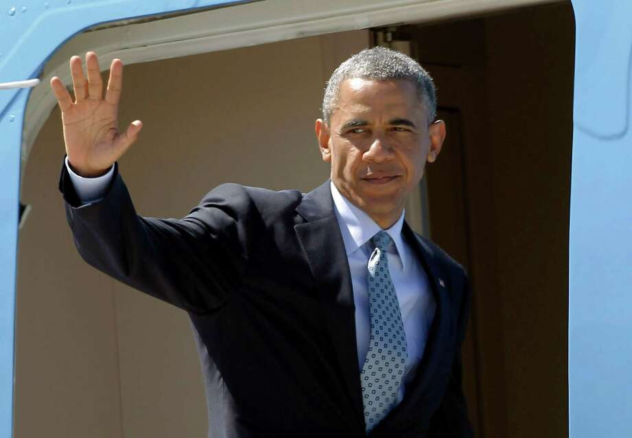 President Barack Obama waves to supporters as he boards Air Force One to return to Washington at Los Angeles International Airport Thursday, July 24, 2014 in Los Angeles. Photo: AP / AP