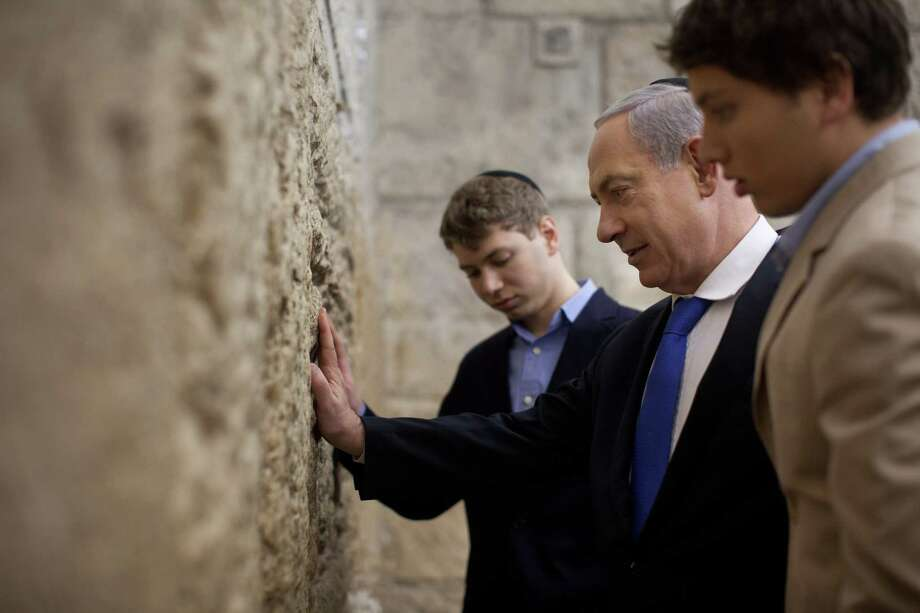 Yair, left, and Avner, far right, pray with their father at the Western Wall, Judaism's holiest site, on January 22, 2013 in Jerusalem. Photo: Uriel Sinai, Getty / 2013 Getty Images