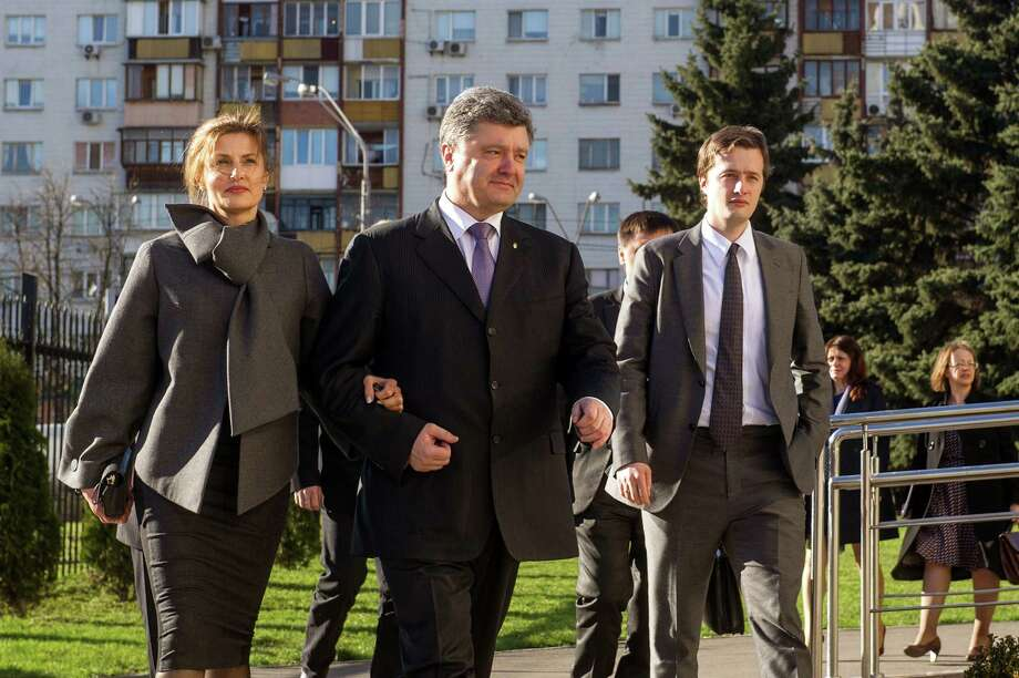 "Oleksiy Poroshenko, son of Ukrainian President Petro Poroshenko Oleksiy, right, walks with dad (center) and his mom, Maryna, left. President Poroshenko made his fortune selling chocolate, allowing snarky journalism types to refer to him as the ""candy king"" or ""munchies mogul."" Not especially relevant, but still—kind of funny to think about. 