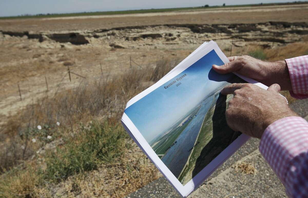 Chase Hurley, General Manager of the San Luis Canal Company, compares a photograph of a flood year at the Eastside Bypass in 2006 to the current bypass in the background July 23, 2014 in Chowchilla, Calif. The sinking ground has brought up concerns with possible flooding into nearby farmland from a dirt canal (Eastside Bypass) designed for routing flood water past the area. Most Central Valley farmers received no more than a 5 percent water allotment this season from government water sources, leaving many farmers with no choice but to pump ground water to keep their businesses afloat.