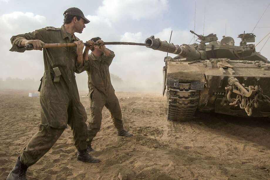 So that's how you load them: Israeli soldiers work on their Merkava tank at an army deployment area 
