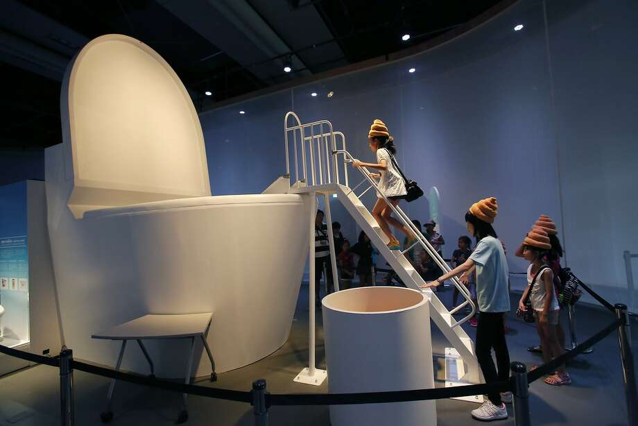 "Japan's toilet fetish is totally out of control: Young visitors wearing ""feces hats"" climb a ladder to the slide 