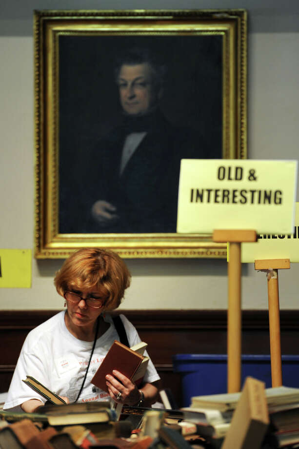 "Barbara Barnett, in town from Atlanta, Ga., checks out some of the ""Old & Interesting"" books at the 54th annual Pequot Library book sale in Fairfield, Conn. July 25, 2014. The sale continues through Tuesday. Photo: Ned Gerard / Connecticut Post"