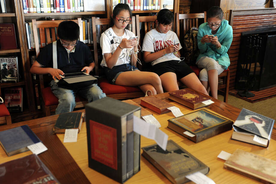 A group of exchange students from China stay glued to their mobile electronic devices as their teacher shops at the 54th annual Pequot Library book sale in Fairfield, Conn. July 25, 2014. The sale continues through Tuesday. Photo: Ned Gerard / Connecticut Post