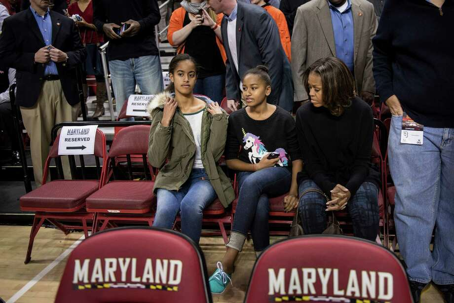 Malia, Sasha and U.S. First Lady Michelle Obama can barely contain their excitement during a University of Maryland basketball game.  Photo: BRENDAN SMIALOWSKI, Getty / 2013 AFP