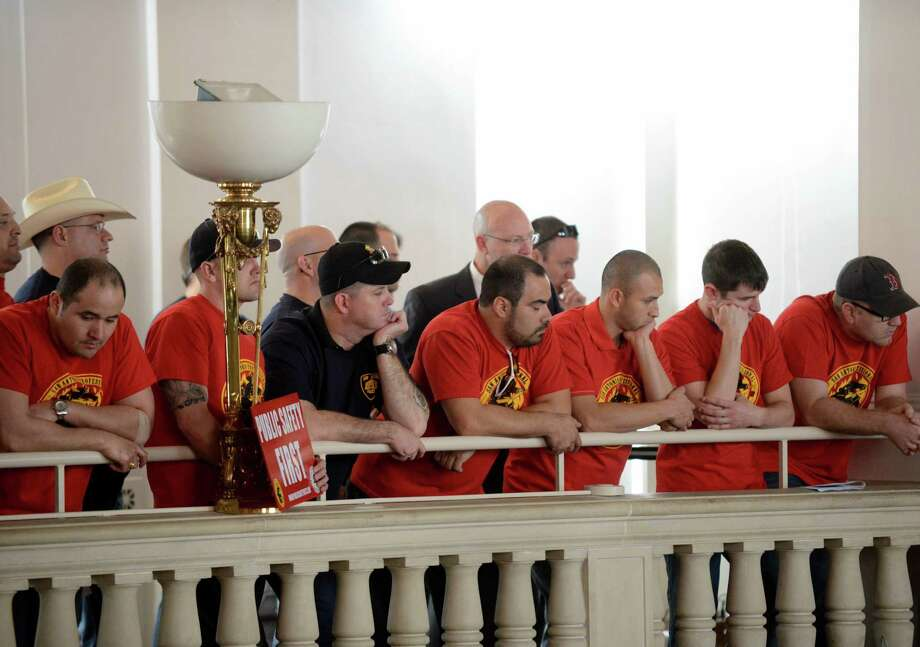 Police and firefighters union members listen as the City Council prepares to hear the recommendations of a task force considering their retirement and health benefits in February. Photo: Billy Calzada / San Antonio Express-News / San Antonio Express-News
