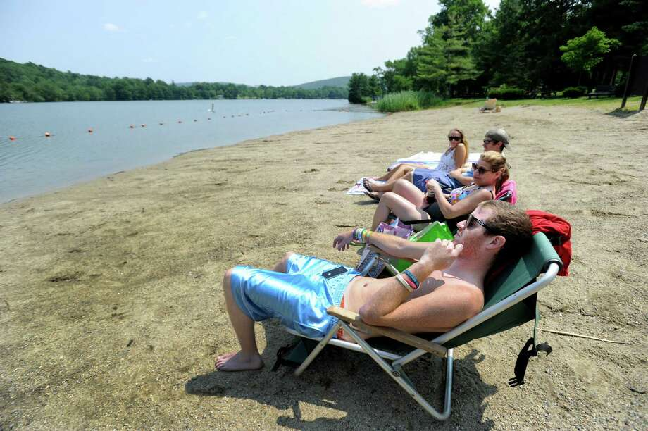 Anne McAndrew,of Kent, Conn.,  her sons, Woody and Mike and friend Megan Faletra, relax at the beach at Lake Waramaug State Park  Friday, July 25, 2014,  unaware of the ban on swimming. Photo: Carol Kaliff / The News-Times