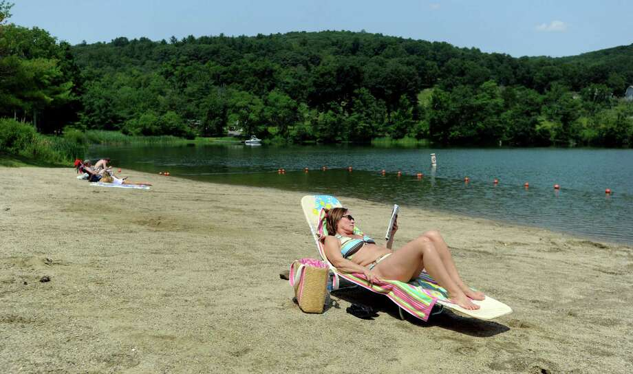 Christine Greenwood of Thomaston, Conn. relaxing on a near-empty beach Friday, unaware the ban on swimming at the Lake Waramaug State Park beach  in Kent, Conn., Friday, July 25, 2014. Photo: Carol Kaliff / The News-Times