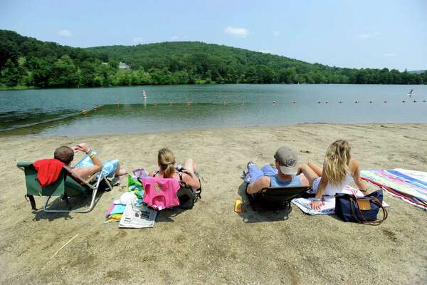 Anne McAndrew,of Kent, Conn.,  her sons, Woody and Mike and friend Megan Faletra, relax at the beach at Lake Waramaug State Park  Friday, July 25, 2014,  unaware of the ban on swimming.