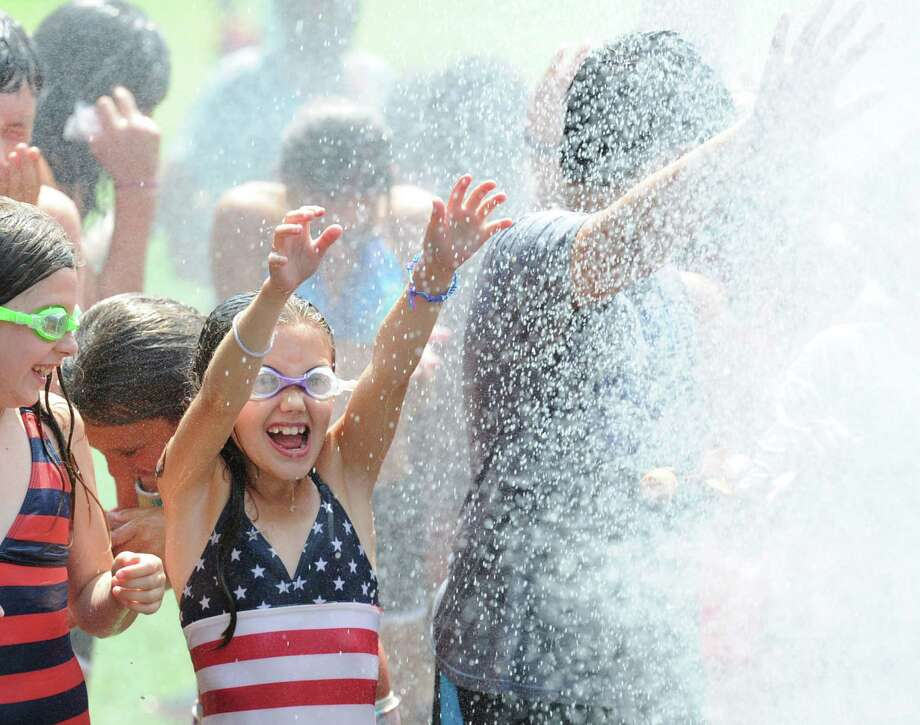 "At center, Lily Atkinson, 9, gets blasted with water shot out of a hose held by Santa during Santa's annual ""Christmas in July"" visit to the Boys & Girls Club of Greenwich Camp Simmons Friday afternoon, July 25, 2014. Photo: Bob Luckey / Greenwich Time"