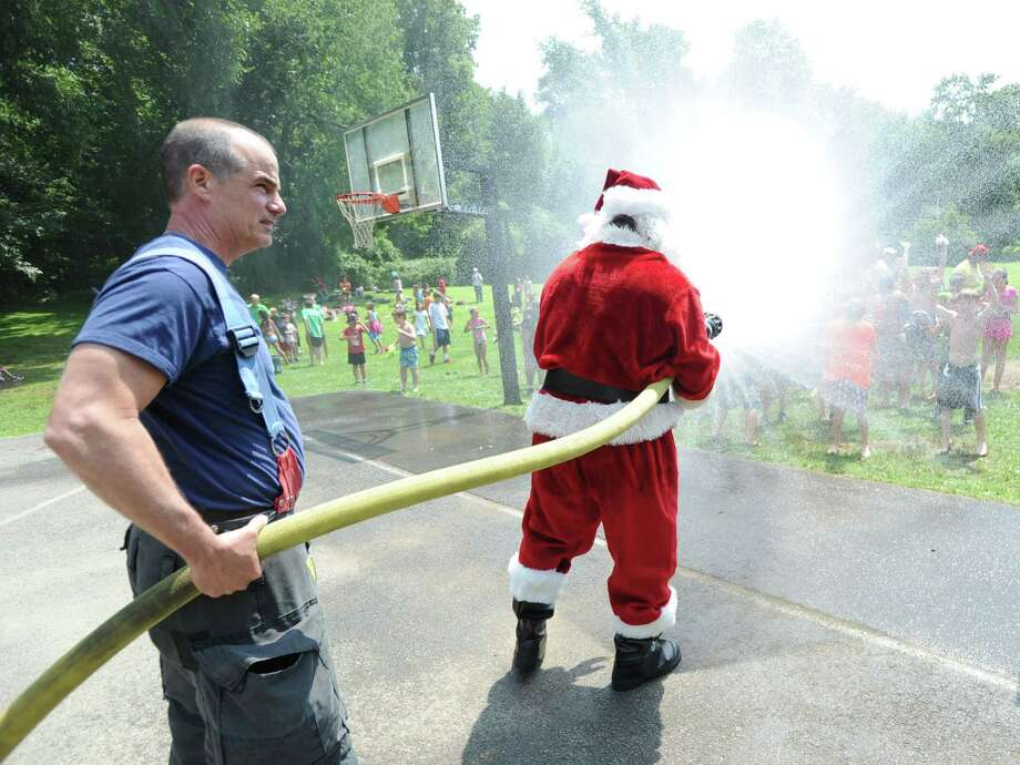 "Santa interacts with campers during his annual ""Christmas in July"" visit to the Boys & Girls Club of Greenwich Camp Simmons Friday afternoon, July 25, 2014. Photo: Bob Luckey / Greenwich Time"