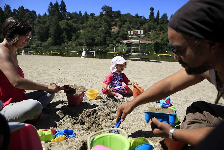 Top: With paddling in the lake off limits, Ariana Johnson, 3, plays in the sand with parents Roslyn and Todd Johnson. Photo: Michael Short, The Chronicle