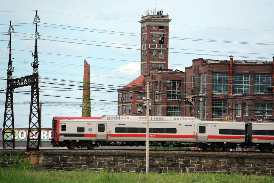 A Metro-North train travels past the former Remington Arms factory, and Shot Tower, in Bridgeport, Conn. July 24, 2014, seen from the vacant Father Panik Village property. A new commuter rail station is planned near this location, tentatively called Barnum Station. Photo: Ned Gerard / Connecticut Post