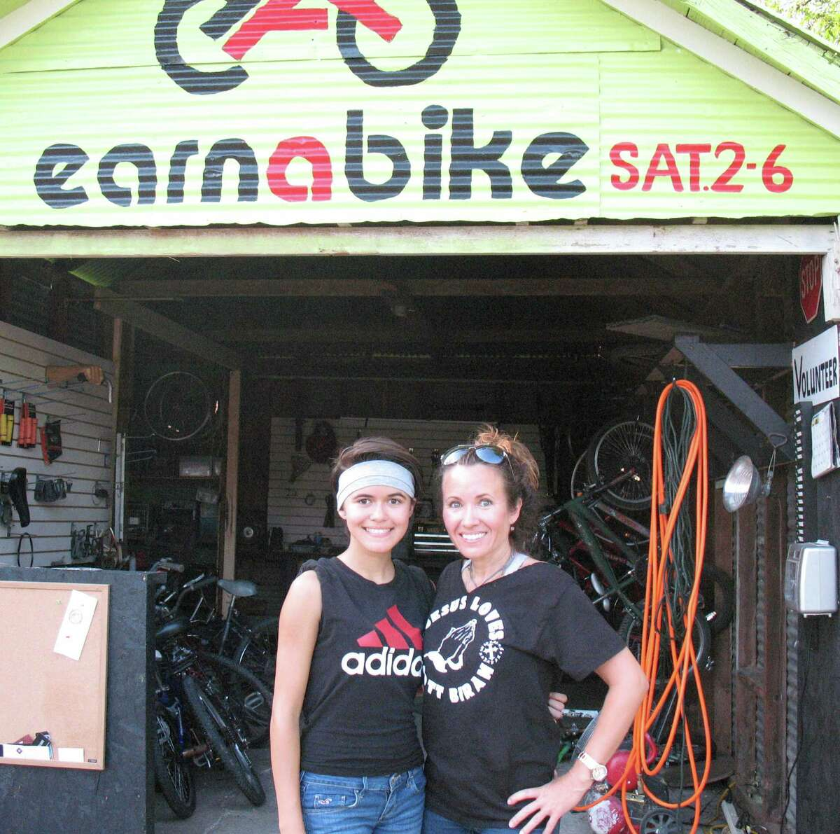 Lydia Boudreaux (right) earned a free bike by working at the Earn-A-Bike Co-op. Her daughter, Jelly, is working to earn her own bike.