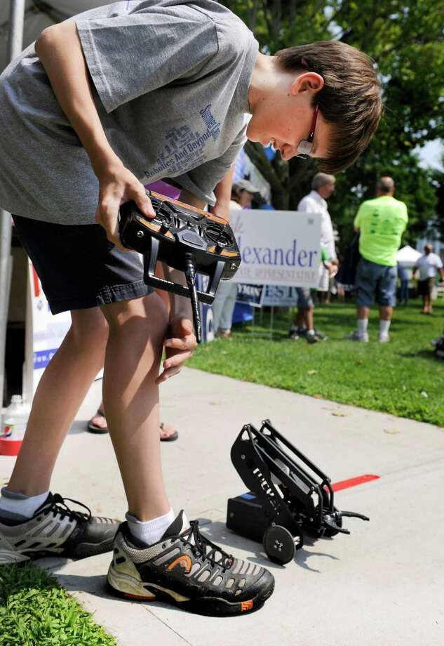 Colby Harrington, 12, of Kent, Conn. works with his robot at the Robotics and Beyond booth at the New Milford Fair Days Friday, July 25, 2014, on the New Milford, Conn. Green. Photo: Carol Kaliff / The News-Times