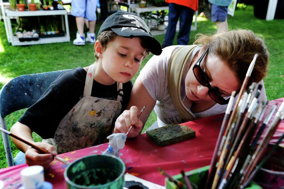 Madox Wodjenski, 8, and his mother, Li, of New Milford, Conn., paint a ceramic dog together at the New Milford Village Fair Days on the green in New Milford, Conn. Friday, July 25, 2014. Photo: Carol Kaliff / The News-Times
