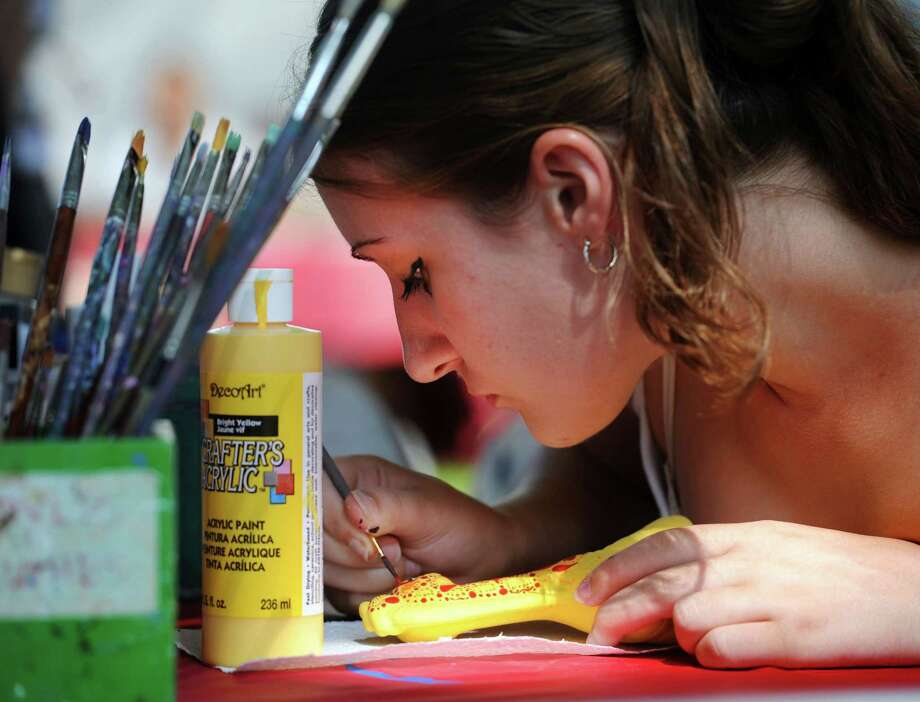 Emily Psenicnik, 22, of New Milford, Conn., paints a ceramic horse at the Village Center for the Arts booth at New Milford Village Fair Days Friday, July 25, 2014. Photo: Carol Kaliff / The News-Times