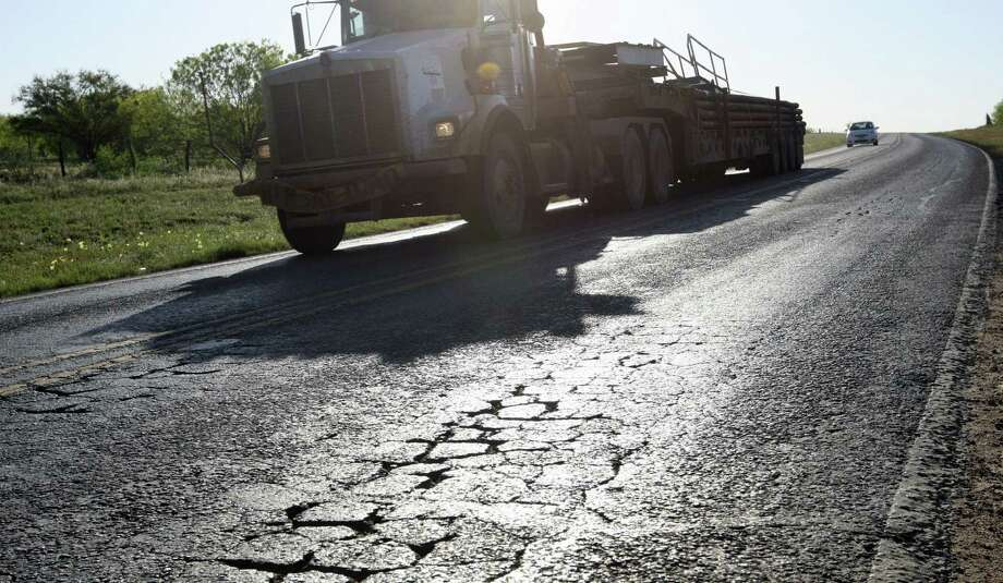 """Oil field traffic moves along FM 468 just northwest of Cotulla. La Salle County and other top oil-producing areas in the Eagle Ford Shale are dealing with road problems including broken chunks of shoulders, potholes and """"alligator"""" cracks. Photo: Jerry Lara / San Antonio Express-News / SAN ANTONIO EXPRESS-NEWS"""